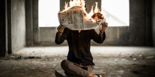 Man reading a news paper while it's burning